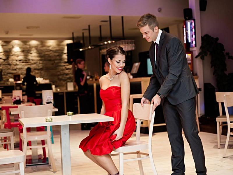 Mężczyzna podsuwa krzesło kobiecie przy stole