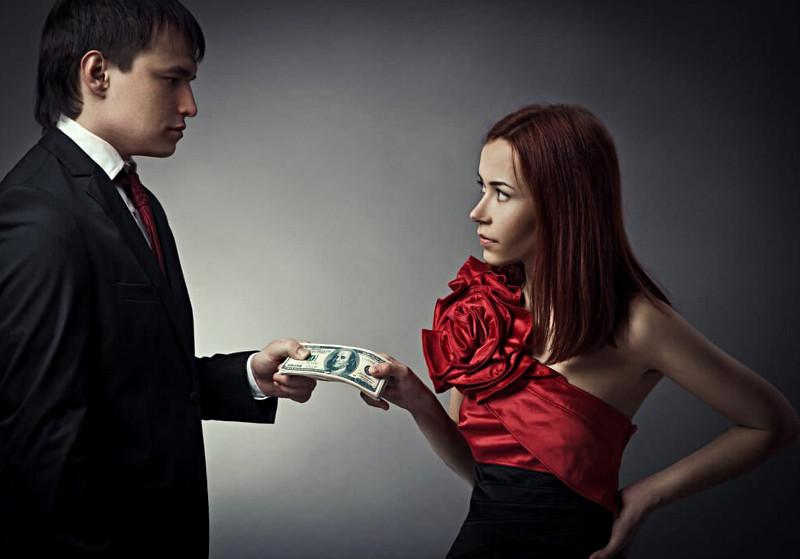 Facet przekazuje pieniądze kobiecie w czerwono-czarnej sukni
